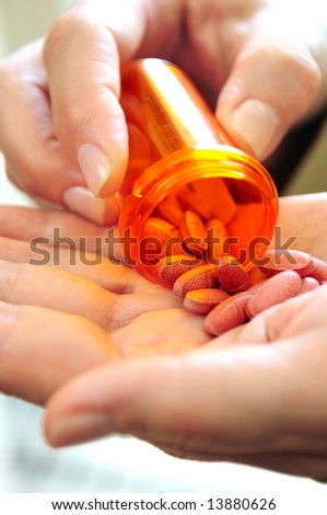Closeup on woman's hands with pills and pill container