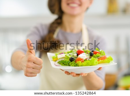 Shutterstock Closeup on woman showing fresh salad and thumbs up
