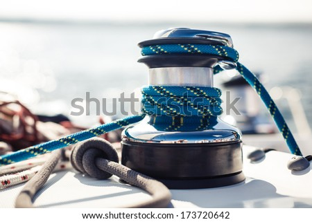 Closeup on yacht cord crank rope holder on white sail background