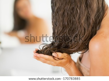Closeup on young woman applying hair mask