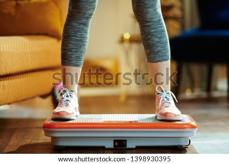 Photo of  Closeup on young woman in fitness clothes in the modern house training using vibration power plate.