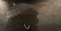 Closeup one transparent umbrella with droplets on white handle and wet street as a background at evening after raining. Loneliness in a rainy day weather change concept with copy space