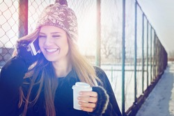 Closeup outdoor portrait of cute happy blonde Caucasian teenage girl with takeaway coffee talking on smartphone. Young woman with long hair with coat, gloves, knitted hat outdoors in winter by fence.