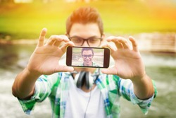 Closeup outdoors shot of young hipster man with headphones taking a selfie with smart phone by the river. Modern teenage guy taking a self portrait outdoors.