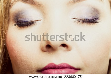 Closeup part of face beautiful female eyes with blue violet make-up visage, applying makeup on eyes