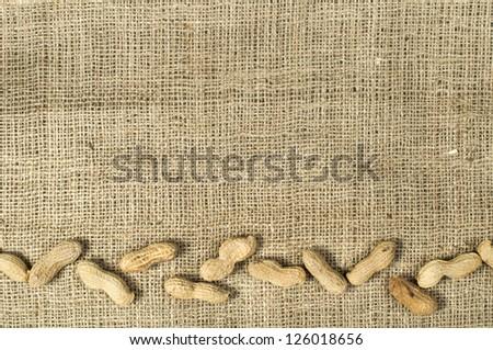 Closeup Peanuts on burlap.Raw peanuts in shells and shelled peanuts. Arranged as border