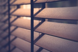 Closeup perspective of a wooden window venetian blinds in the bedroom in morning twilight or dusk which give the warm romantic and cozy retro mood. Beautiful natural light.