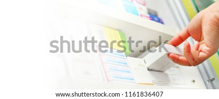 Closeup pharmacist hand holding medicine box in pharmacy drugstore.Space for text on white background