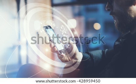 Closeup photo businessman relaxing modern loft office.Man sitting in chair at night.Using contemporary smartphone,blurred background. Digital Connections World Wide Interfaces.Horizontal,film effect
