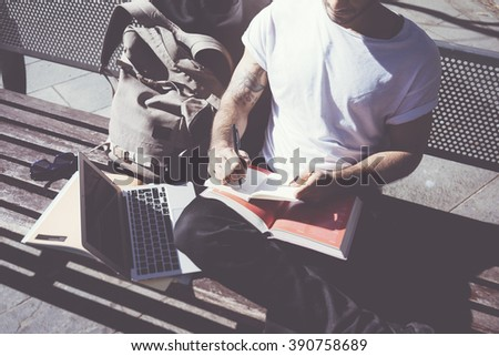 Closeup photo man wearing white tshirt sitting city park and writing notebook. Studying at the University,  preparation for exams. Books, generic design laptop, backpack bench. Horizontal, film effect