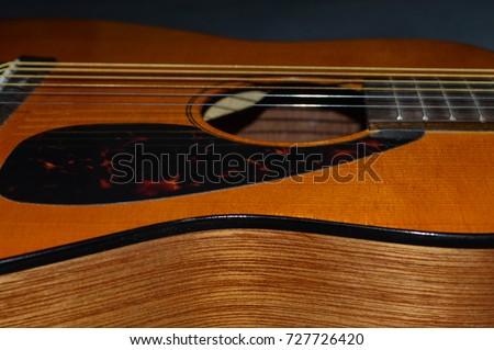 Closeup photo of a child's acoustic guitar body and sound hole and pic guard