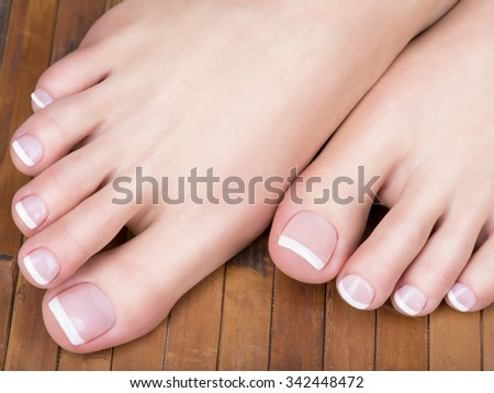 Closeup Photo Of A Female Feet With White French Pedicure On Nails At Spa Salon