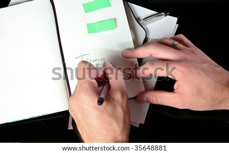 Closeup Photo Of A Man Taking Notes In His Agenda