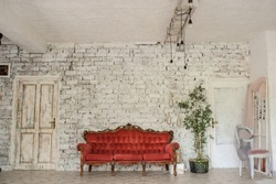 Closeup photo of a red vintage sofa on a white and brown brick wall sorrounded by plants, candles, a chair with a pink curtain on it in a light and large room