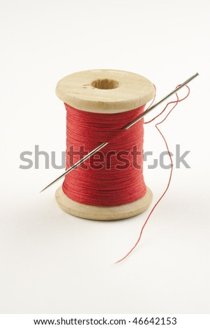 Closeup photo of a spool with red thread and a needle, photographed against a light background for isolation