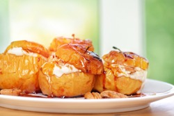Closeup photo of a tasty baked apples stuffed with cheese cream, flavored with cinnamon, nuts and honey, served on the white plate, healthy nutrition, delicious fruit dessert
