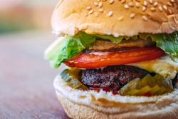 Closeup Photo of a Tasty Big Burger. Fast Food. Delicious Unhealthy Food. Juicy Grilled Ground Meat with Fresh Vegetables and Bun. Traditional American Cuisine.