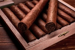 Closeup photo of a wooden box with cuban cigars and space for text