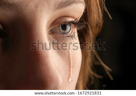 closeup photo of a young woman crying with a tear running down her cheek. Foto stock ©