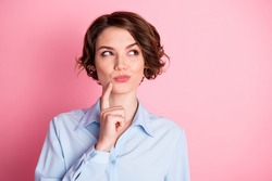 Closeup photo of attractive charming lady arm finger on chin look tricky side up empty space cunning smart intelligent person wear blue office shirt isolated pink pastel color background