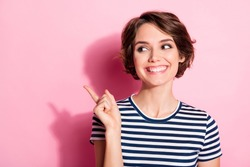 Closeup photo of attractive funny lady look side empty space indicate finger sale prices product banner wear casual white blue t-shirt isolated pastel pink color background