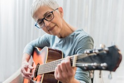 Closeup photo of beautiful mature woman practicing guitar playing, Music lessons concept