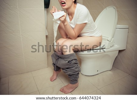 closeup photo of beautiful sweet woman having constipation problem sitting on bathroom toilet seat and holding tissue paper with making suffering emotion.
