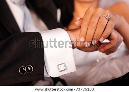 Closeup photo of bride and groom hands with engagement ring.?