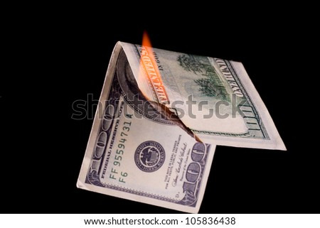 Closeup photo of burning dollar banknote on black background