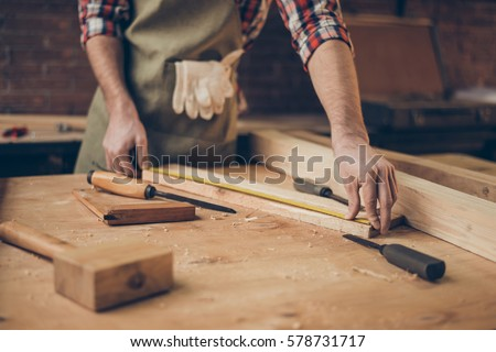 closeup photo of  cabinetmaker's tabletop.  Craftsman holding ruler  on wooden planknear other tools. Photo stock ©