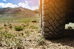 Closeup photo of car wheel on steppe terrain