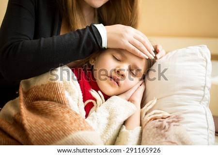 Closeup photo of caring mother holding head on sick daughter forehead #291165926