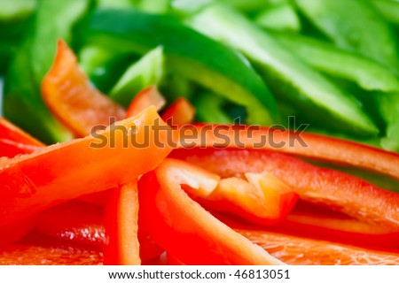 Closeup photo of chopped red and green peppers with short depth of field, and focus on the red peppers.