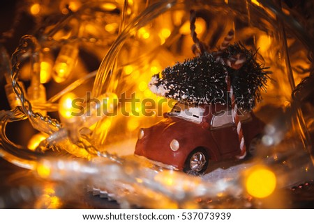 Stock Photo Closeup photo of christmas glass toy with cars and tree. Yellow garland background