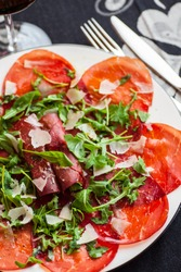 Closeup photo of dish with italian bresaola and ruccola. Selective focus - shallow depth of field.