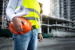 Closeup photo of engineer with hardhat and blueprints posing on building site