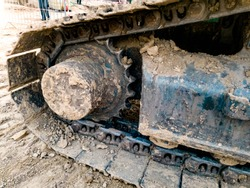 Closeup photo of excavator tracks covered in dirt on the construction site