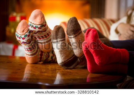 Stock Photo Closeup photo of family feet in wool socks at fireplace