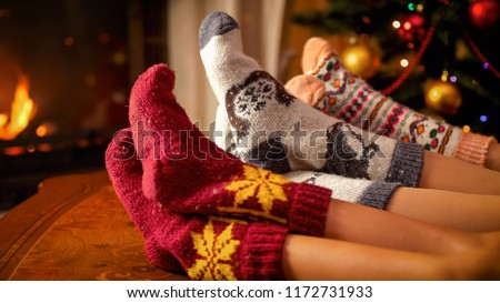 Closeup photo of family in warm knitted socks lying next to fireplace and Christmas tree