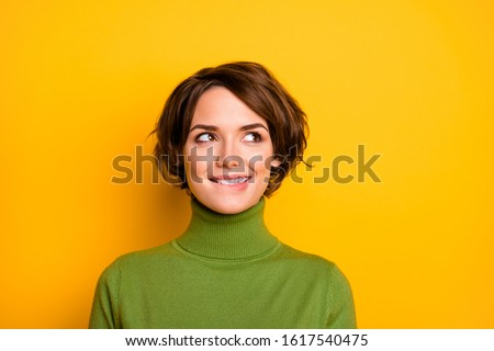 Closeup photo of funny pretty lady charming smiling good mood looking side empty space biting lips wear casual green warm turtleneck isolated yellow color background