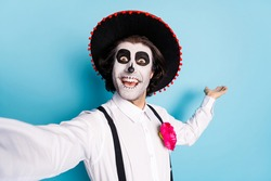 Closeup photo of funny traditional zombie creature guy death day creepy scary makeup mask masquerade make selfies show banner advert wear latin hat costume isolated blue color background