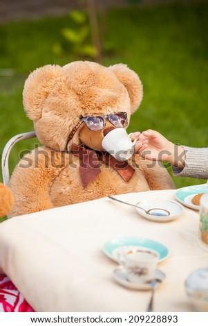 Closeup photo of girl giving tea to teddy bear in sunglasses