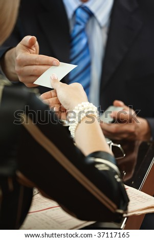 Closeup photo of hands exchanging business card.