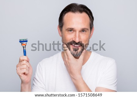 Closeup photo of handsome mature handsome man looking mirror use razor going to shave beard metrosexual neat guy wear white t-shirt isolated grey color background