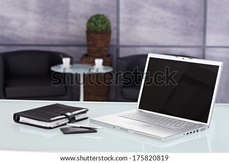 Closeup photo of laptop, personal organizer and mobilephone placed on desktop in office.