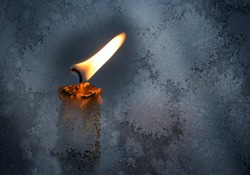 Closeup photo of little candle flame behind frozen window glass