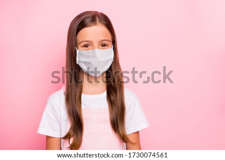 Closeup photo of little cute lady keep self-isolation wear fabric mask rose overall white t-shirt isolated pink background
