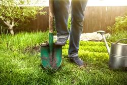 Closeup photo of man holding foot on shovel at garden at sunny day