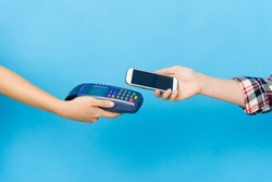 closeup photo of mobile pay with credit card machine and cell smart phone isolated on blue background.