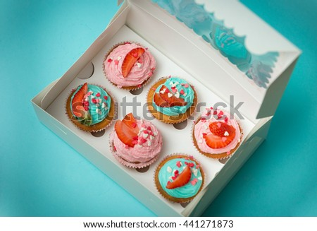Closeup photo of open paper box with six colorful cupcakes